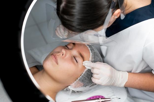 Esteticista realizando procedimento de microblading em uma mulher