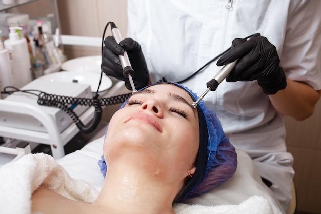 Esteticista realizando procedimento de microcorrente no cliente
