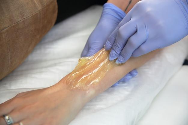 Esteticista remove o cabelo da mão de uma mulher.
