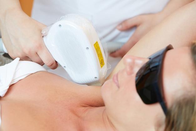 Esteticista, removendo o cabelo da jovem mulher com laser