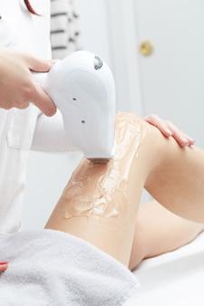 Esteticista removendo o cabelo da perna da mulher jovem com laser