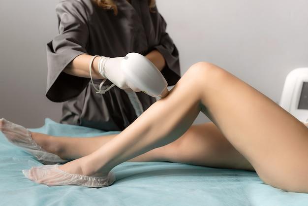 Esteticista removendo pelos em pernas finas de mulheres usando um laser