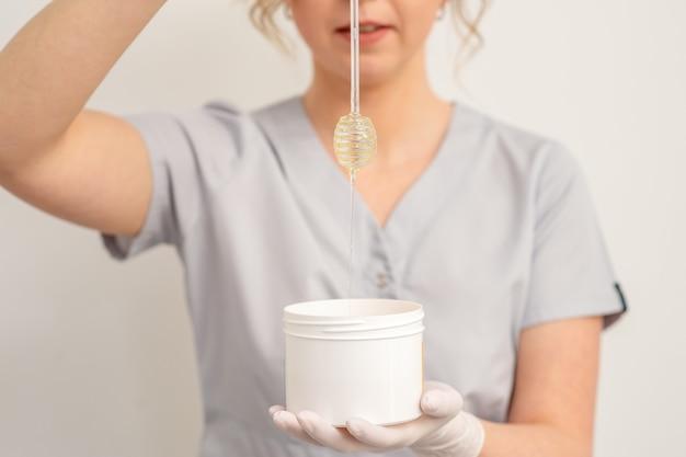Esteticista segurando uma tigela branca com cera escorrendo de um bastão de mel em uma parede branca