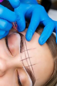 Esteticista tatuando as sobrancelhas de uma mulher usando equipamento especial durante a maquiagem definitiva, close-up.