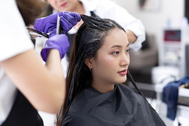 Esteticistas asiáticos estão tingindo o cabelo e fazendo o cabelo para os clientes.