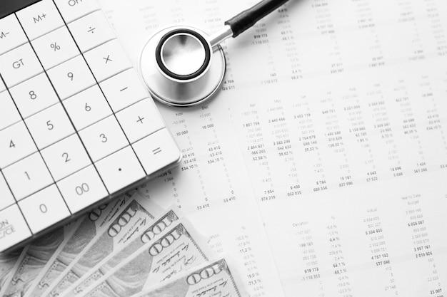 Estetoscópio, calculadora e dinheiro em espécie com dados médicos. conceito de custos de saúde ou seguro médico