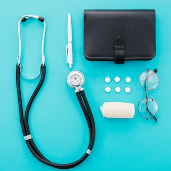 Estetoscópio; caneta; pílulas; diário; óculos e curativo em fundo azul