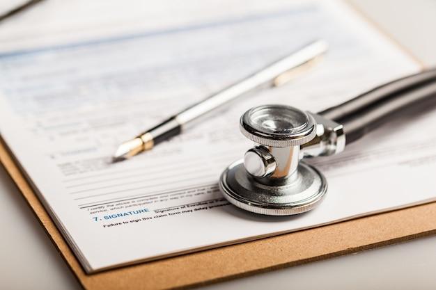 Estetoscópio, caneta-tinteiro e documentos médicos em tablet de madeira