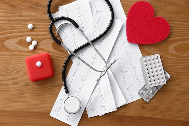 Estetoscópio, cardiogramas, pílulas e coração vermelho na mesa na clínica