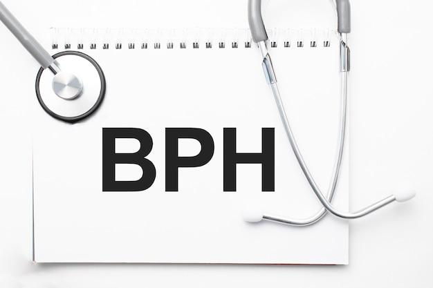 Estetoscópio cinza e placa de papel com uma folha de papel branco com texto bph fundo azul claro. conceito médico.