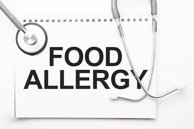 Estetoscópio cinza e prato de papel com uma folha de papel branco com fundo azul claro do texto alergia alimentar. conceito médico.
