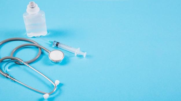 Estetoscópio com ampolas e seringa no pano de fundo azul