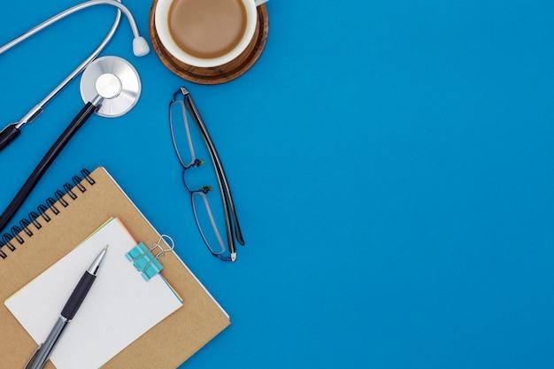 Estetoscópio com caderno, caneta, papel branco, xícara de café, copos, sobre fundo azul