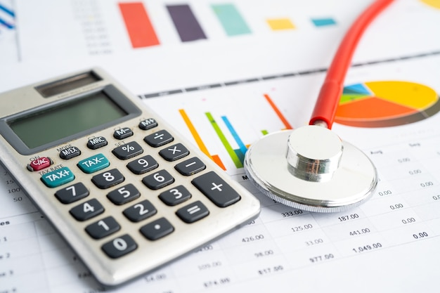 Estetoscópio com calculadora na conta de finanças de papel milimetrado