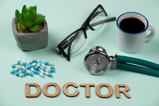 Estetoscópio com comprimidos, óculos e café