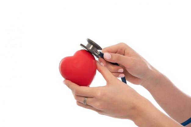 Estetoscópio com coração nas mãos do médico isoladas no close-up branco, copyspace, cuidados médicos.