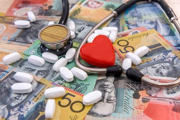 Estetoscópio com coração vermelho e comprimidos em dólares australianos