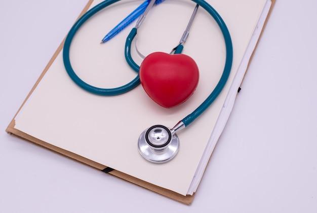 Estetoscópio com coração vermelho e placa de folha no fundo branco