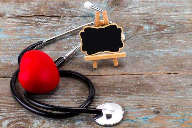 Estetoscópio com coração vermelho e quadro-negro com espaço vazio para um texto em madeira