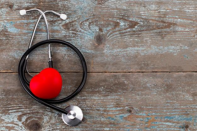 Estetoscópio com coração vermelho em uma madeira com espaço de cópia