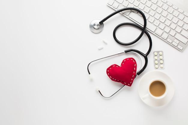 Estetoscópio com coração vermelho perto de medicamentos; xícara de café e teclado sobre a mesa branca
