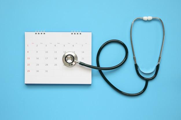 Estetoscópio com data de página de calendário em fundo azul conceito médico de consulta médica