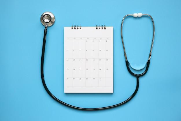 Estetoscópio com data de página de calendário na mesa azul, conceito médico de consulta médica