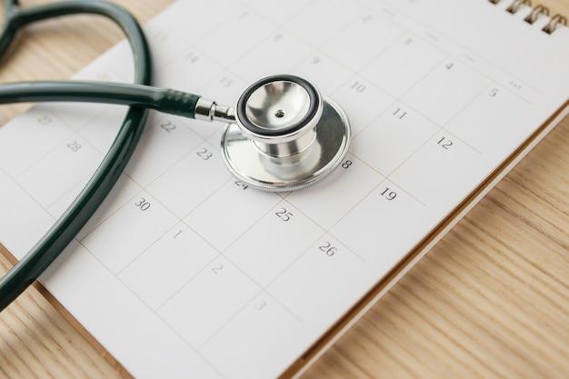Estetoscópio com data de página de calendário na parede de mesa de madeira conceito médico de consulta médica