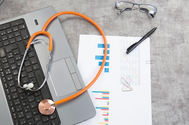 Estetoscópio com documentos financeiros sobre a mesa e um laptop