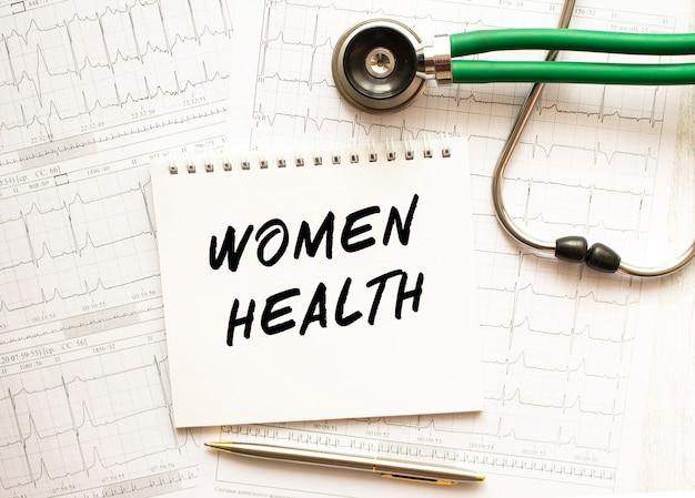 Estetoscópio com eletrocardiograma e bloco de notas com o texto saúde da mulher.