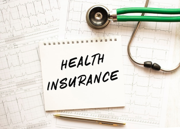 Estetoscópio com eletrocardiograma e bloco de notas com o texto seguro de saúde. conceito de cuidados de saúde.