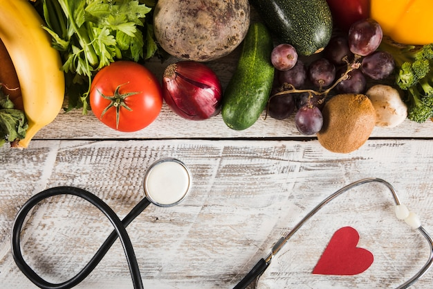 Estetoscópio com forma de coração perto de legumes frescos em fundo de madeira