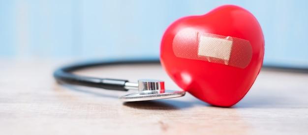 Estetoscópio com forma de coração vermelho. cuidados de saúde, seguros e conceito do dia mundial do coração