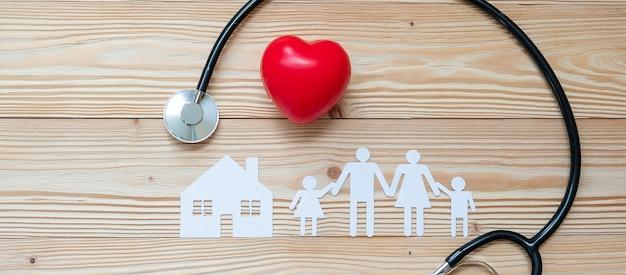 Estetoscópio com forma de coração vermelho, família e papel de casa