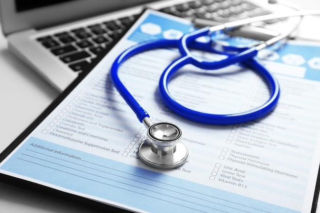 Estetoscópio com formulário médico e laptop