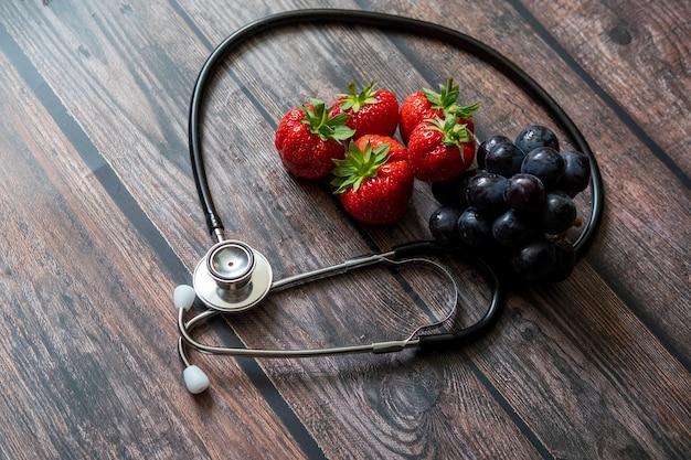 Estetoscópio com morangos e uva preta sem sementes em cima da mesa de madeira.