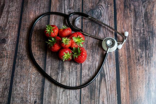 Estetoscópio com morangos e uva sem sementes preta em cima da mesa de madeira. conceitual médico e de saúde.