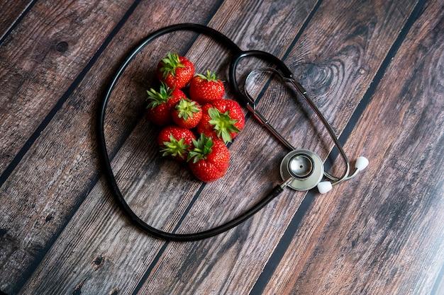 Estetoscópio com morangos em cima da mesa de madeira. conceitual médico e de saúde.
