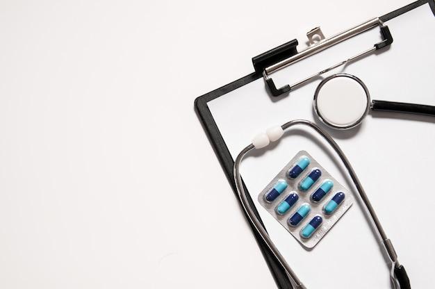 Estetoscópio com pílulas de remédio na prancheta médica, conceito médico. conceito de cuidados de saúde.