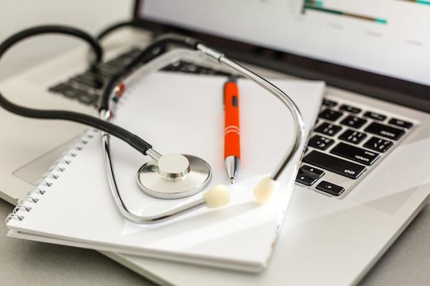 Estetoscópio com prancheta e laptop na mesa, médico trabalhando.