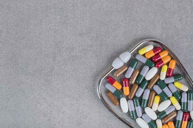 Estetoscópio com várias pílulas coloridas na superfície cinza