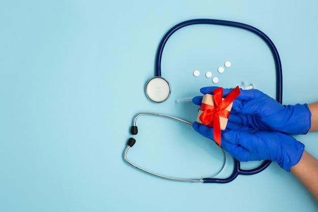 Estetoscópio, comprimidos e caixa de presente em fundo azul.