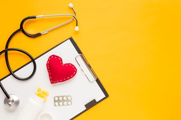 Estetoscópio; coração costurado; medicamento caindo de garrafas; blister embalado medicina com prancheta sobre a mesa amarela
