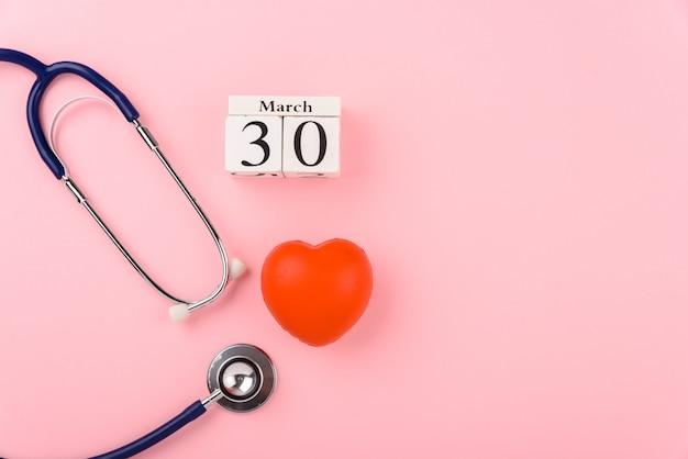 Estetoscópio, coração vermelho e calendário