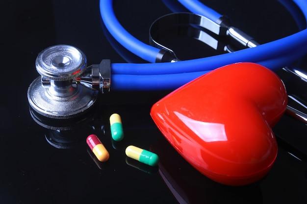 Estetoscópio, coração vermelho e pílulas sortidas no espelho preto b