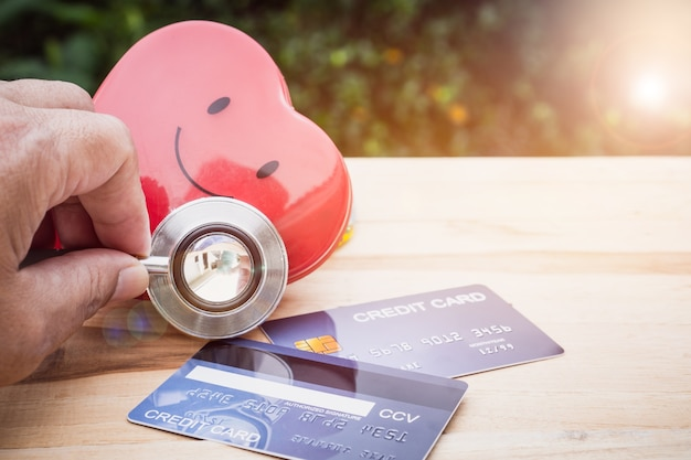 Estetoscópio de coração sorriso vermelho na mock up cartão de crédito com titular na mesa de madeira hospital