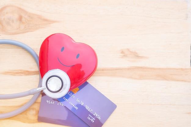 Estetoscópio de coração vermelho sorriso no mock up cartão de crédito com titular no hospital
