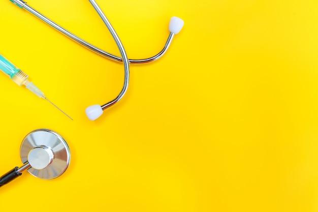 Estetoscópio de equipamento de medicamento e seringa isolados na mesa amarela