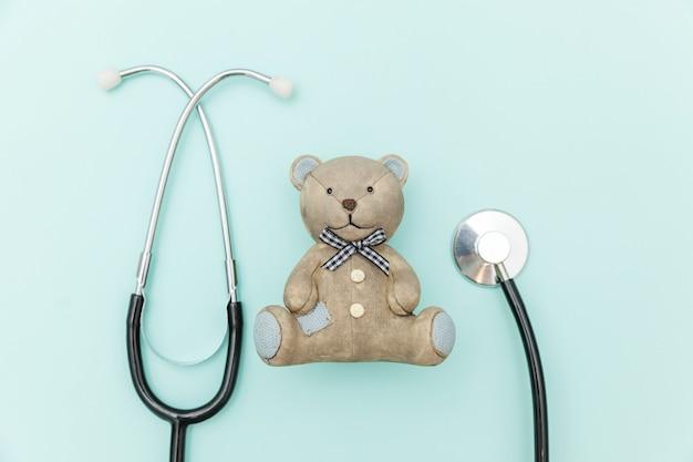 Estetoscópio de equipamento de medicina e urso de brinquedo isolado em azul pastel