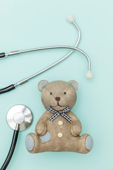 Estetoscópio de equipamento de medicina e urso de brinquedo isolado em fundo azul pastel